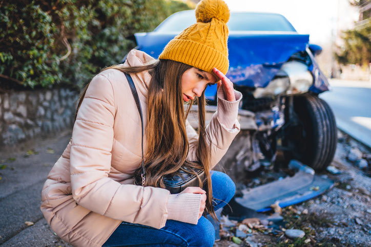 Frustrated woman next to wrecked car